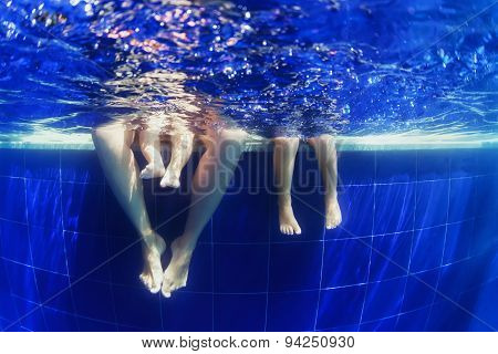 Underwater Photo Of Happy Family Swimming In The Blue Pool