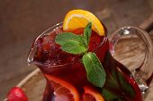 foto of jug  - Wine of Sangrija in a transparent jug on a wooden table with an orange and a strawberry - JPG