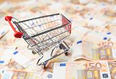 picture of fifties  - Tiny shopping cart over the surface covered with the multiple fifty euro bank notes  - JPG