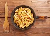 foto of french fries  - Cooking fried french potatoes composition of an old iron pan - JPG