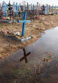 picture of cemetery  - Flooded rural cemetery graves and display the cross in the water - JPG