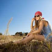 stock photo of tallgrass  - Beautiful hippie looking girl sitting on a meadow  - JPG