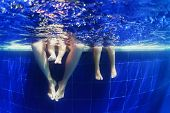 image of young baby  - Young mother swimming underwater with fun in pool with baby boy and the little girl. Active family lifestyle and children water sports activity with parents during summer vacation on tropical resort ** Note: Visible grain at 100%, best at smaller sizes - JPG