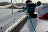picture of reinforcing  - Black Carbon fibre reinforcement on Sailboat with reflection and water drops  on the surface, it is the fast racing boat. Whiches and other sailing equipment in the background. - JPG