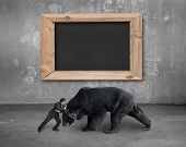 picture of stop fighting  - Businessman fighting against black bear with blank blackboard on concrete wall background - JPG