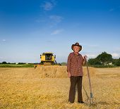 picture of combine  - Old farmer with hat and hayfork standing on field during harvest combine harvester in background - JPG