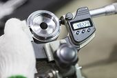stock photo of micrometer  - operator inspection high precision automotive part by micrometer - JPG