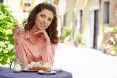 image of croissant  - Portrait of beautiful blond woman sitting in outdoors cafe in Italy - JPG