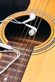 stock photo of risque  - Close up earphone on guitar  - JPG
