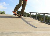 image of skateboard  - closeup of skateboarder legs skateboarding at skatepark ramp - JPG
