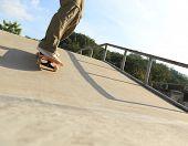picture of skateboard  - closeup of skateboarder legs skateboarding at skatepark ramp - JPG