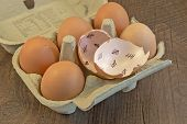 stock photo of count down  - Egg shells shown lying on a wooden background with marks inside counting down the days till hatching - JPG