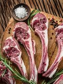 image of lamb chops  - Raw lamb chops with garlic and herbs on the old wooden table - JPG