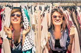 stock photo of stall  - Young beautiful women at the weekly cloth market  - JPG