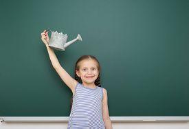 picture of schoolgirl  - Schoolgirl with watering can near the school board - JPG