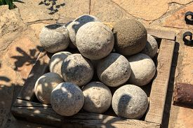 stock photo of cannon-ball  - Many of historical old cannon balls heap of stone balls - JPG