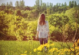 image of girl walking away  - Young woman walking away through the meadow holding yellow flowers - JPG