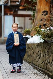 stock photo of japan girl  - Adorable little girl kimono at street of resort town in Japan going to public hot spring spa - JPG