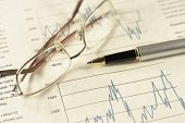 Financial charts pen and glasses.