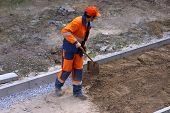 a worker with a shovel throws building material