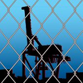 silhouette crane outline with city skyline with wire fence