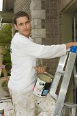Young man, holding a can of paint and ladder