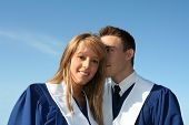 Cute couple in graduation gowns.