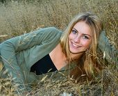 Beautiful teenage girl laying in tall grass.