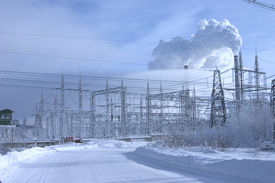 foto of power lines  - Powerful power station costing in an environment of snowdrifts on a background of the blue sky - JPG