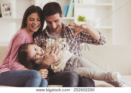 poster of Young Family Having Fun. Together At Home. Happy Childhood. Attractive Young Couple. Parents And Kid