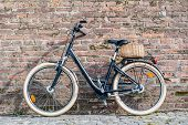 Black Retro Vintage Bicycle With Old Brick Wall And Copy Space. Retro Bicycle With Basket In Front O poster