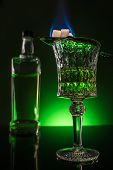 Glass And Bottle Of Absinthe With Burning Sugar On Spoon On Reflective Surface And Dark Green Backgr poster