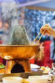 Chinese Traditional Hot Pot Hot Pot With A Hand With Chopsticks poster