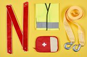 Flat Lay With Arranged First Aid Kit And Automotive Accessories Isolated On Yellow poster