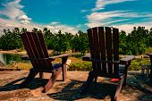 Two Muskoka Chairs Sitting On A Wood Dock Facing A Calm Lake. Across The Water Is A White Cottage Ne poster
