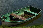 Small Wooden Boat Without Oars In Summer.small Wooden Boat Without Oars Anchored On The Grassy Shore poster