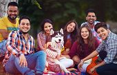 Portrait Of Happy Friends Chilling Together With Pet Dog In Park poster