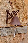 Постер, плакат: Возрасте ржавого железа мало колокол висит из каменной стены на Майорке