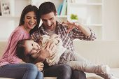 Young Family Having Fun. Together At Home. Happy Childhood. Attractive Young Couple. Parents And Kid poster