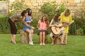 Female Music Teacher With Pupils Having Music Lesson Outdoors. Music Band Of Teen Girls With Musical poster