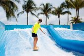 Teenager Surfing In Beach Wave Simulator Attraction In Water Amusement Park Of Tropical Resort. Teen poster