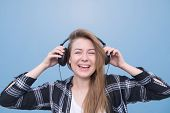 Close Portrait Of A Happy Girl Who Listens To Music In Headphones On A Blue Background, Looks Into T poster