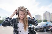 Street Portrait Of A Girl In Casual Clothing, Walking Around The City With Headphones And Listening  poster