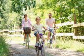 family, leisure and people concept - happy mother, father and little daughter riding bicycles in sum poster