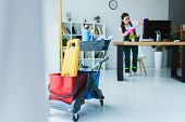 Young Female Janitor Cleaning Office With Various Cleaning Equipment poster