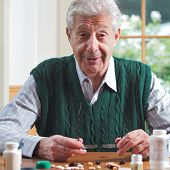 Senior Man Looks Up From Many Pills On A Table