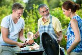 stock photo of bbq party  - Family having a barbecue party in their garden in summer - JPG