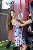 foto of caboose  - Attractive teenage girl in a dress standing on the steps of a red caboose