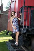 pic of caboose  - Attractive teenage girl in a dress standing on the steps of a red caboose - JPG