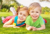 Picture of brother and sister having fun in the park, two cheerful children laying down on green gra